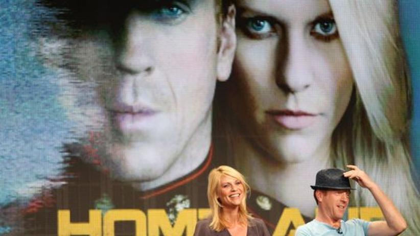 """Claire Danes und Damian Lewis vor einem Plakat von """"Homeland"""""""