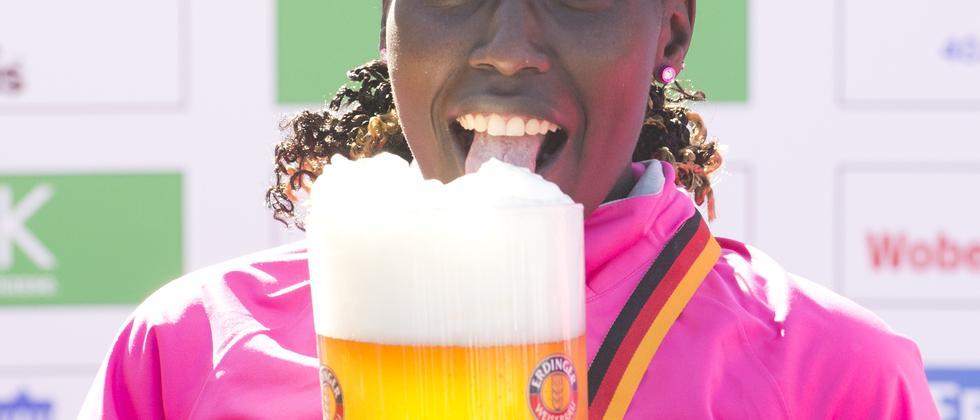 Florence Kiplagat, Gewinnerin des Berlin Marathon 2013, feiert mit einem Glas Bier
