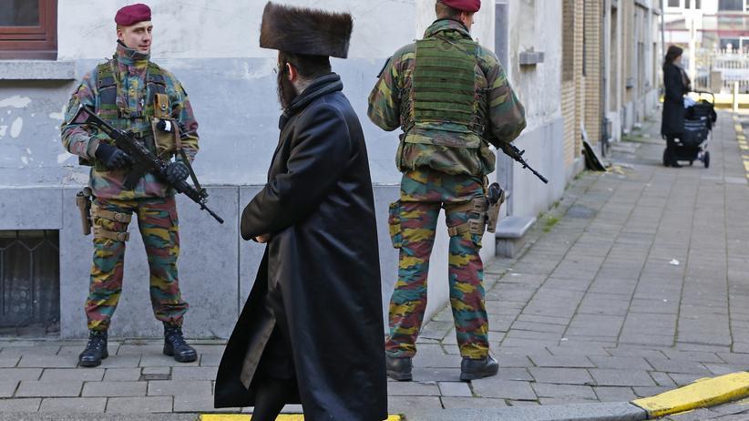 Belgien: Belgische Soldaten und ein traditionell gekleideter orthodoxer Jude im jüdischen Viertel von Antwerpen