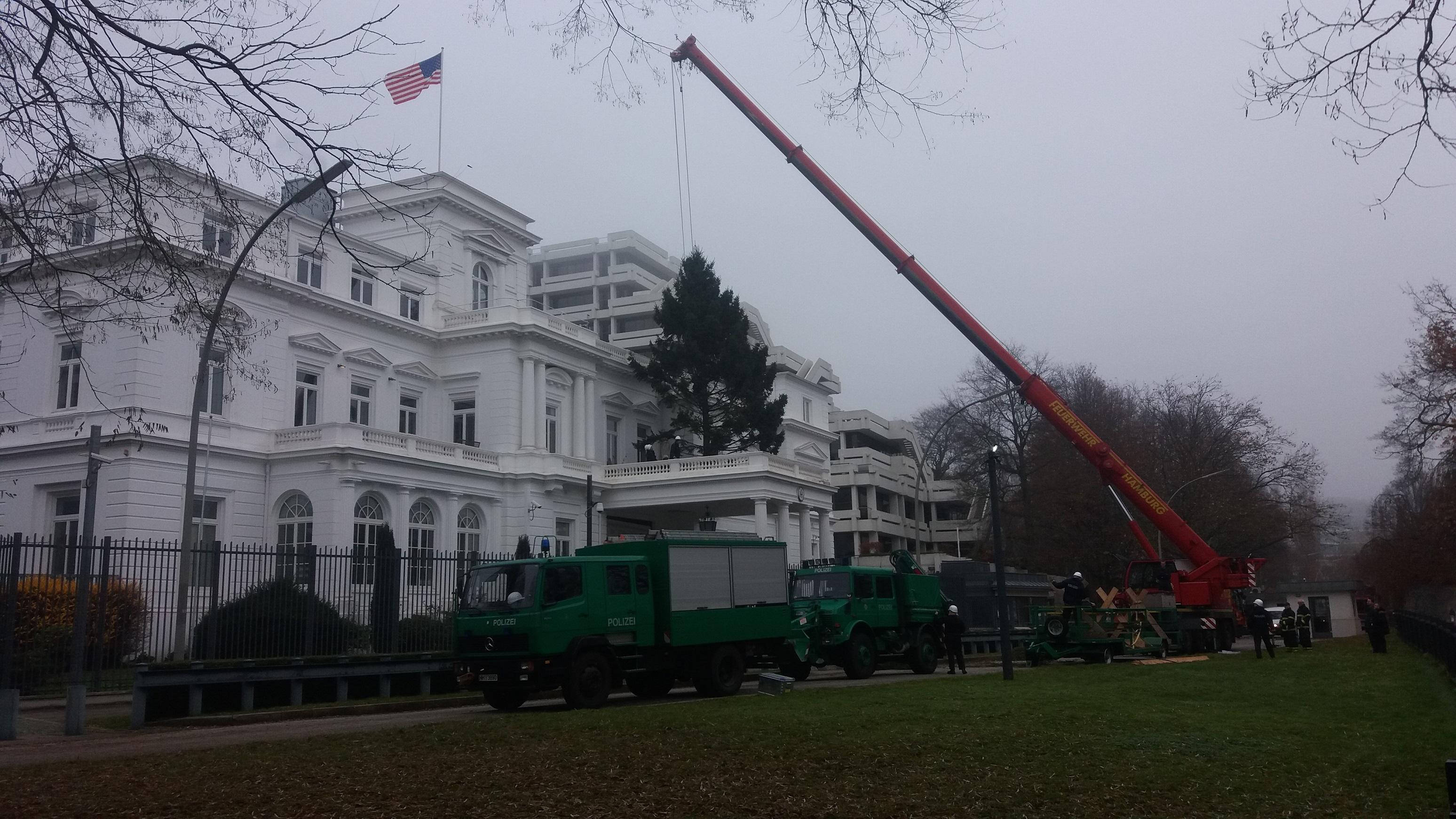 Der Kran ist von der Feuerwehr, die Trucks sind von der Polizei.  Da waren bestimmt ein Dutzend Beamte im Einsatz. Es ging wohl tatsächlich nur darum, den Baum auf den Balkon des US-Konsulats zu hieven ...