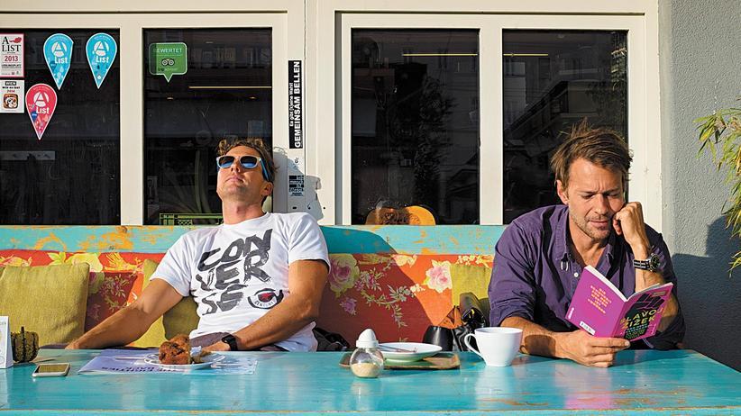 Zwei Männer sitzen vor dem Wiener Martkcafé in der Sonne