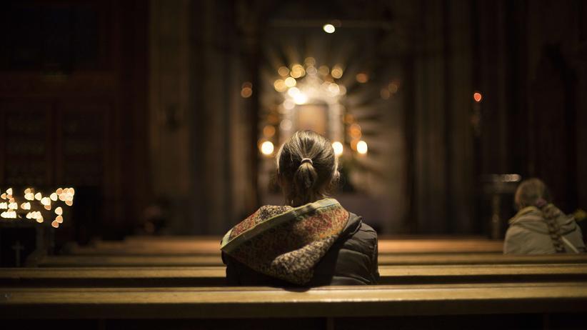 Eine Frau betet im Stephansdom in Wien