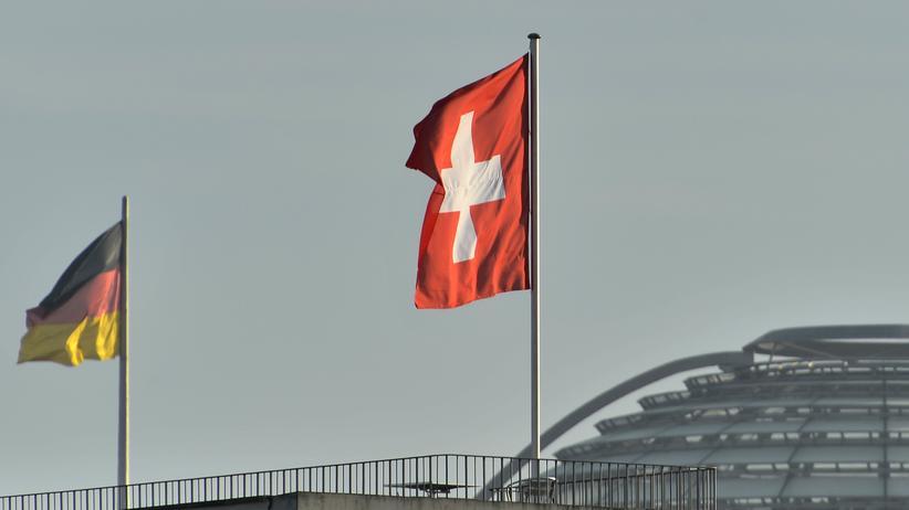 Steuerhinterziehung: Die schweizer Flagge auf der schweizer Botschaft und im Hintergrund die Reichstagskuppel mit der deutschen Flagge.