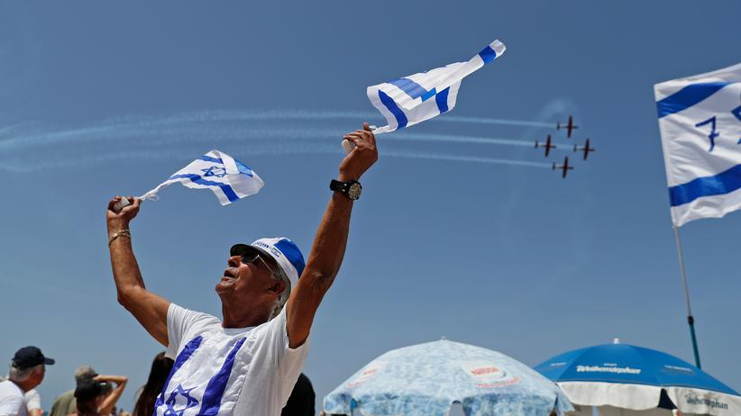Unabhängigkeitstag Israel: Ein Mann mit Israelflaggen beobachtet die Flugshow der israelischen Luftwaffe zum Unabhängigkeitstag.