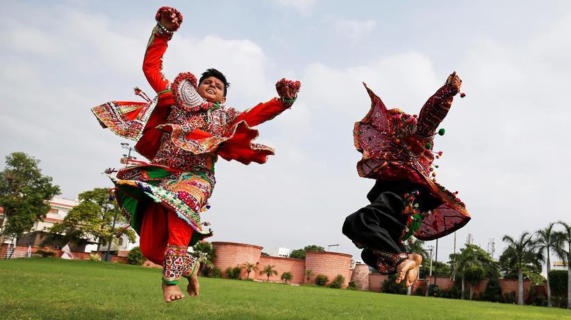 """""""Fremdheit"""": Darsteller in traditioneller Kleidung proben einen Volkstanz für das hinduistische Fest Navratri in Indien."""
