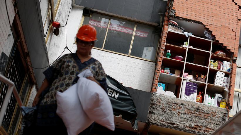 Mexiko: Eine Frau bringt einige Habseligkeiten aus einem zerstörten Gebäude.