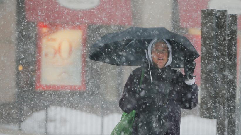 Wintersturm: Mit Regenschirm und dicker Winterbekleidung schützt sich eine Frau in Boston vor Kälte und Schnee.