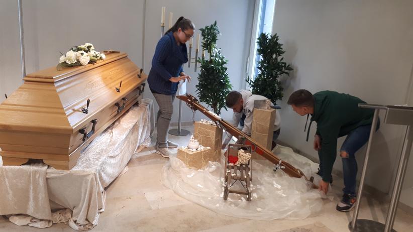 Bestatter: Mit Schlitten und Skiern dekorieren die Auszubildenden eine Trauerfeier.