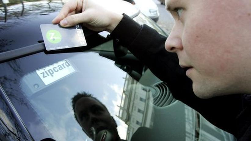 Ein Mann, der in London Carsharing nutzt, hält eine elektronische Karte gegen die Windschutzscheibe des Fahrzeugs