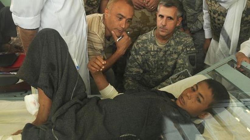 Gregory Smith (M.), Kommunikationsdirektor der Isaf, besuchte eines der Opfer des Luftangriffs im Krankenhaus in Kundus. Der Junge wurde bei dem Beschuss durch die Nato an Armen und Beinen verletzt