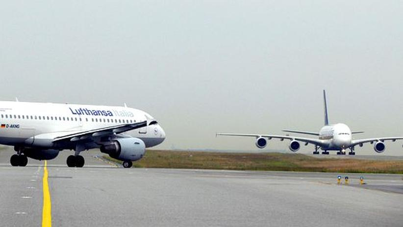 Ein Lufthansa-Airbus wartet auf dem Pariser Flughafen Roissy Charles de Gaulle, ein Airbus A380 der Singapore Airlines landet gerade