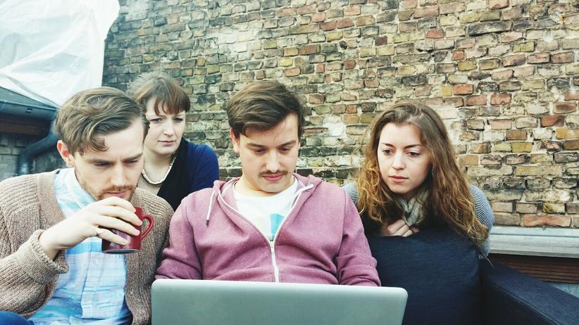 Eine Gruppe junger Menschen schaut auf einen Computer