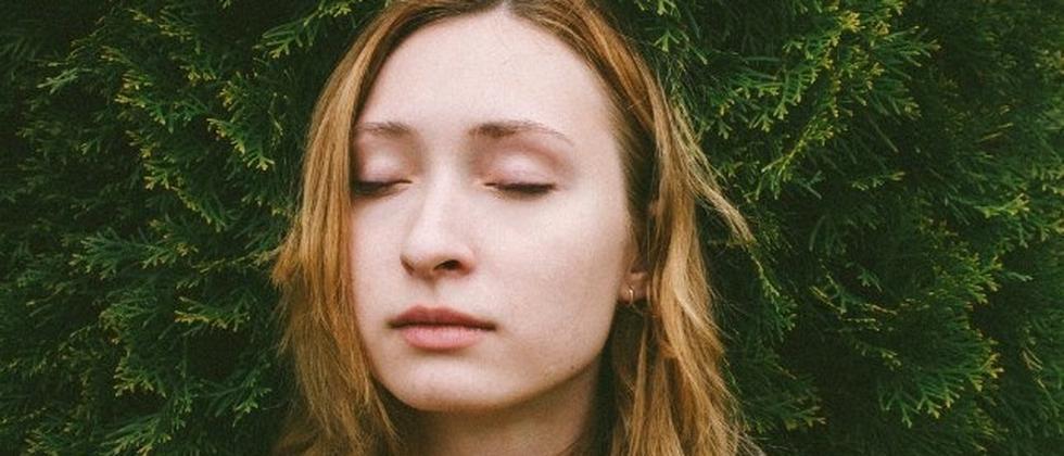 Eine junge Frau schließt die Augen
