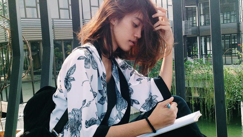 Eine junge Frau sitzt und zeichnet