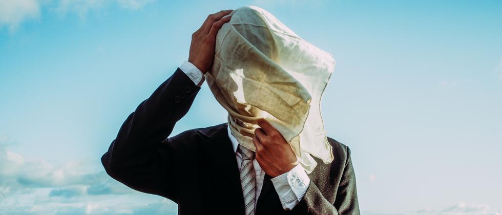 Ein Mann im Anzug mit Tuch vor dem Gesicht