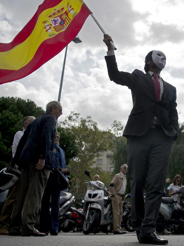 Katalonien: A masked demonstrator against independence waves a Spanish flag during a protest in front of Catalunya Radio headquarters in Barcelona on September 27, 2017.