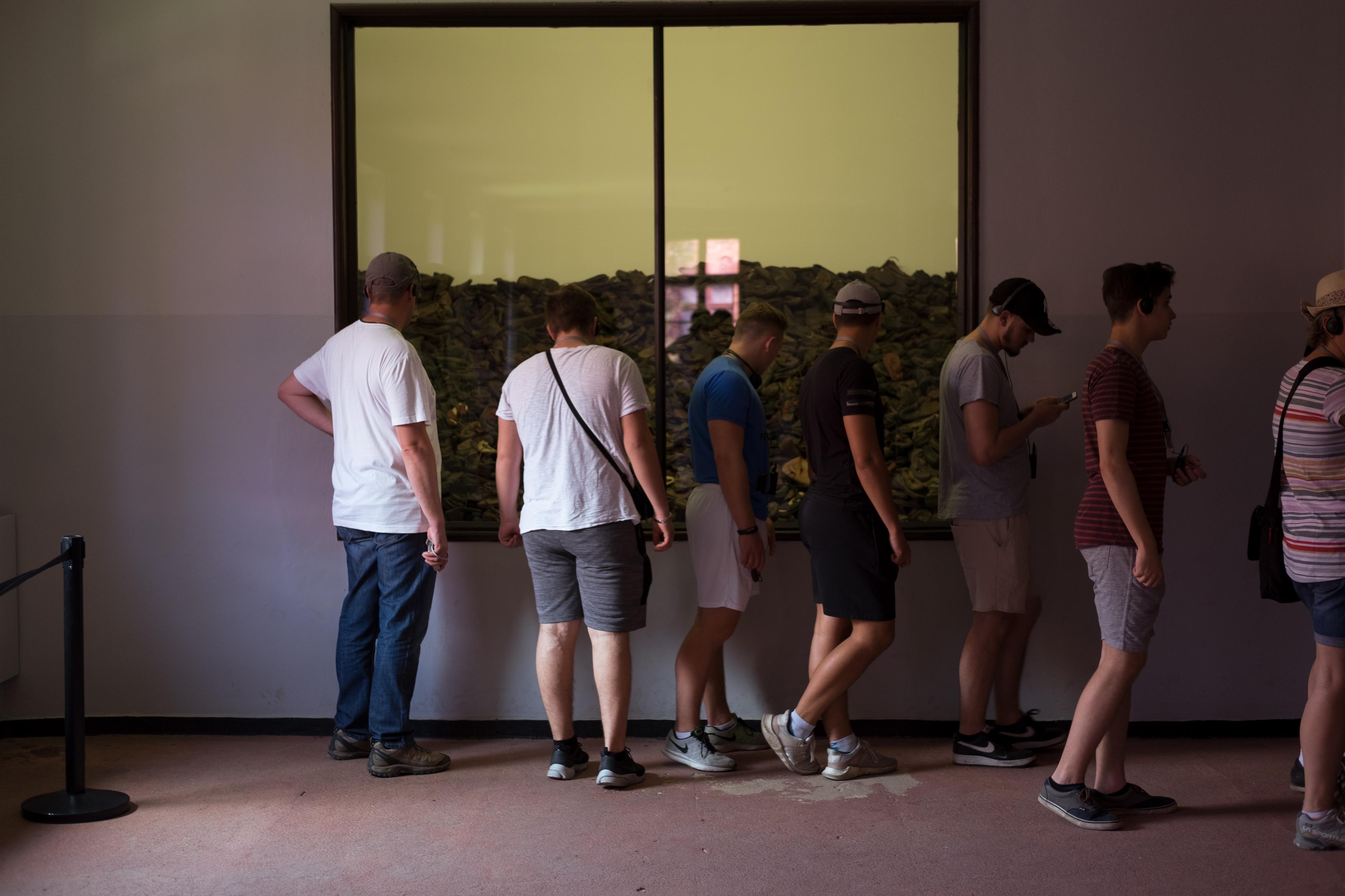 Holocaust: Berat (2. v. l.) und die anderen Jungs besichtigen die Ausstellung im Stammlager Auschwitz I. Hinter dem Fenster sind Schuhe von getöteten Häftlingen zu sehen.