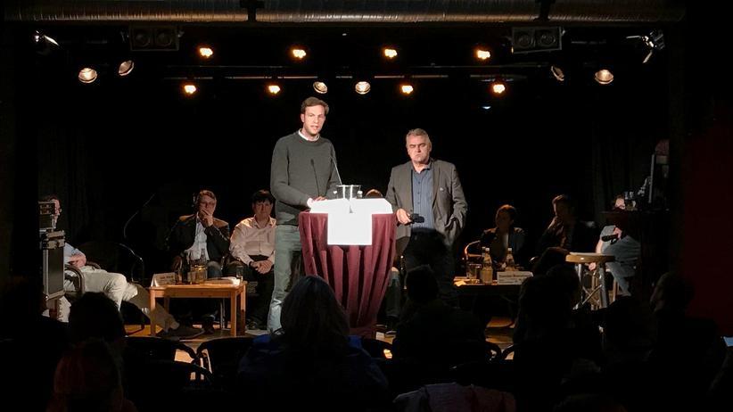 Volt: Damian Boeselager steht mit dem Kandidaten einer anderen Partei auf der Bühne im Parkclub Fürstenwalde. In dem silbernen Weinkühler vor ihnen liegen Zettel mit Fragen über Europa.
