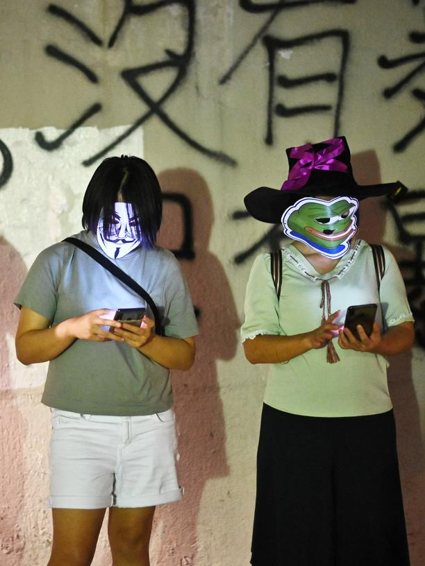 Hongkong: Masked protesters look at their mobile phones as they take part in a human chain rally in Hong Kong's Sha Tin district  on October 18, 2019. - Hong Kong has been battered by more than four months of sometimes violent unrest that have battered the economy, sparked by a now-shelved bill allowing extraditions to the mainland but have since morphed into a movement demanding greater democracy and police accountability. (Photo by Philip FONG / AFP) (Photo by PHILIP FONG/AFP via Getty Images)