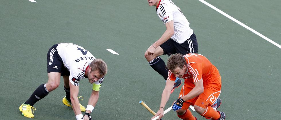 Hockey-WM 2014: Die deutschen Spieler Maximilian Müller und Oliver Korn kämpfen mit dem Niederländer Constantijn Jonker um den Ball.