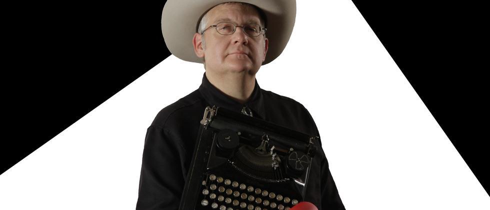 Eric T. Hansen mit Hut, Boxhandschuhen und Schreibmaschine