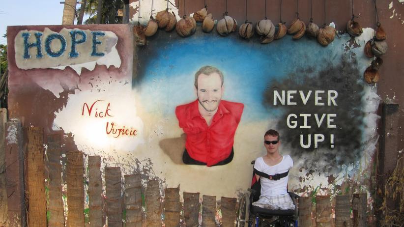 Autor Janis McDavid vor einem Porträt des Motivationsredners Nick Vujicic