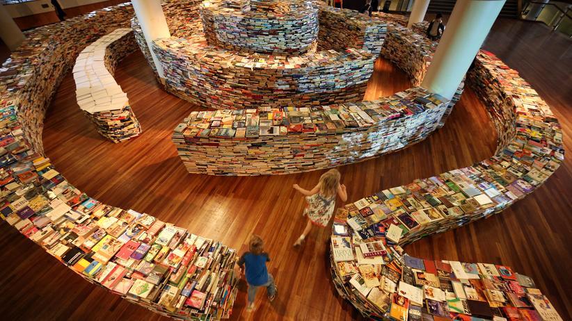 Kinder spielen in einem von brasilianischen Künstlern aus 250.000 Büchern errichteten Labyrinth.