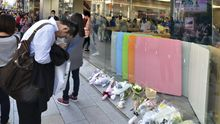 Ein Passant verbeugt sich vor den Blumen, die am Apple-Laden in Tokyo auf der Straße liegen.
