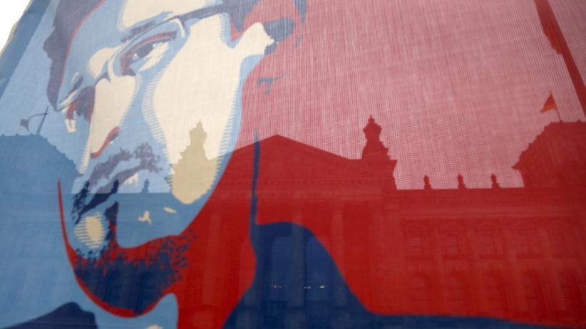 Spionage: Flagge mit Bild Edward Snowdens während einer Demo in Berlin