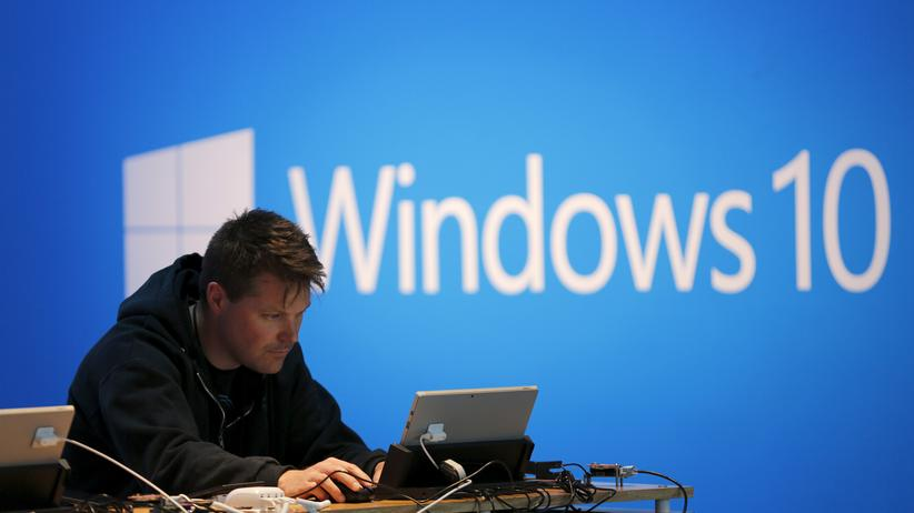 Ein Mann am Laptop vor einem Display mit Windows 10 in San Francisco