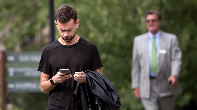 Twitter: Jack Dorsey guckt skeptisch auf sein Handy. Wie kriegt man nur den ganzen Hass von der eigenen Plattform runter?
