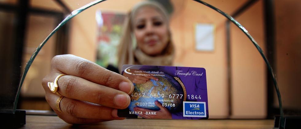 Eine Frau zeigt ihre Kreditkarte.