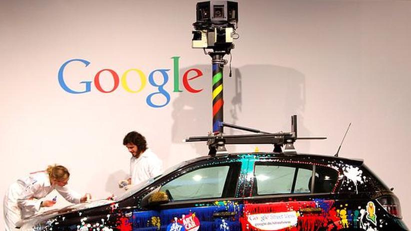 Künstler bemalen auf der CeBit einen der Wagen, mit denen Google die Aufnahmen für Street View fertigte