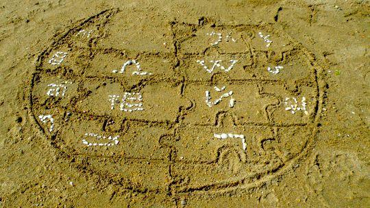 Das Wikipedia-Logo mit Muscheln verziert in den Sand gemalt