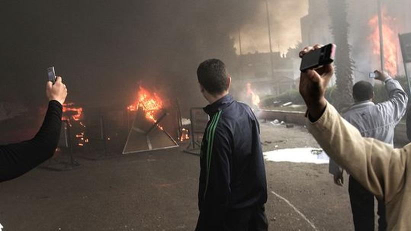 Ägypter fotografieren in Kairo mit ihren Handys eine brennende Polizeistation