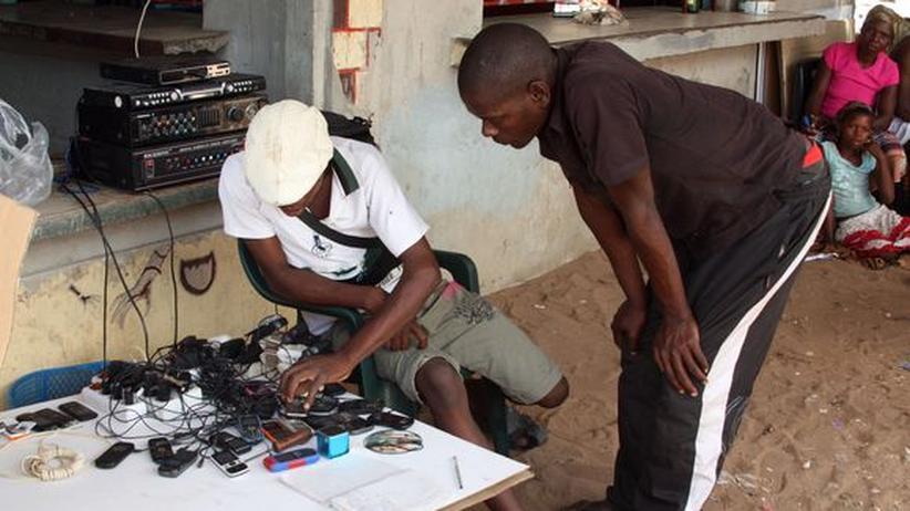 Handyladestation an einer Straße in Mosambique. In Afrika haben mehr Menschen ein Mobiltelefon als Zugang zu Strom.