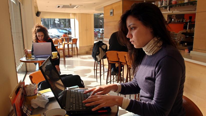 Störerhaftung: Eine Frau arbeitet in einem Café.