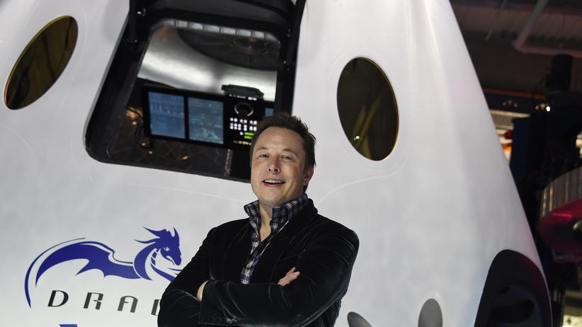 SpaceX-Gründer Elon Musk posiert vor einem Weltraumtransporter.