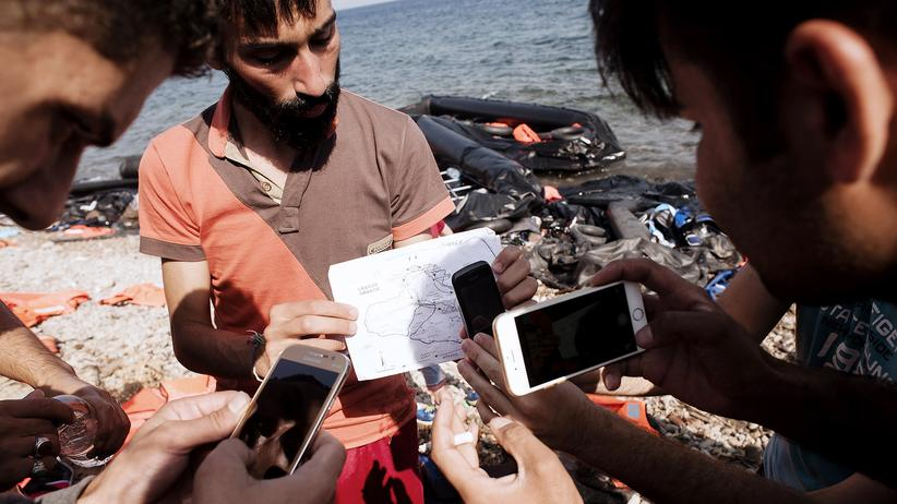Refugees take photos of a map at the Greek island of Lesbos.