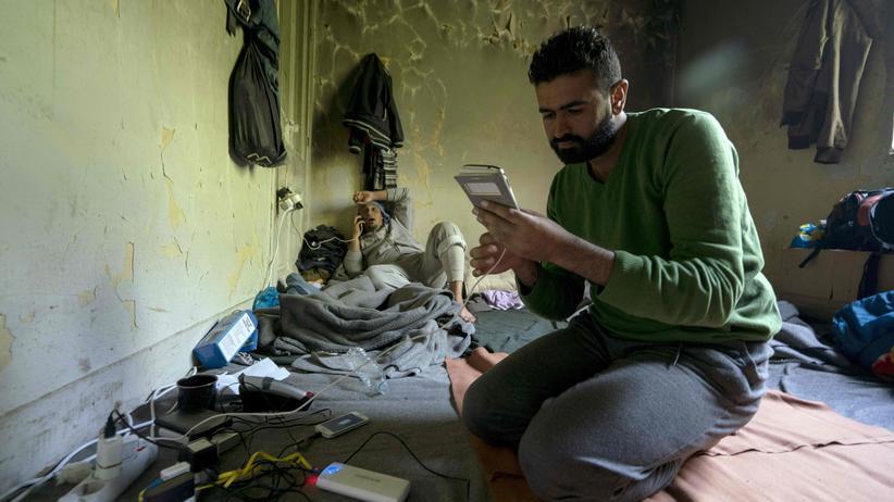 Flüchtlinge laden ihre Smartphones im improviesierten Flüchtlingscamp Idomeni.