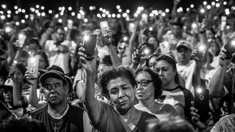 8chan: Der Hass gedeiht online und entlädt sich in der echten Welt: Trauernde in El Paso halten ihre Handys hoch, um der Toten des Anschlags zu gedenken.