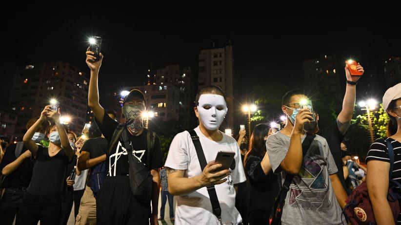 Hongkong: Prodemokratische Aktivistinnen und Aktivisten in Hongkong mit Masken leuchten mit ihren Handys auf einer Demonstration Hongkong im Distrikt Sham Shui Po. Mit der App hkmap.live können die Demonstrierenden sehen, wo die Polizei steht.