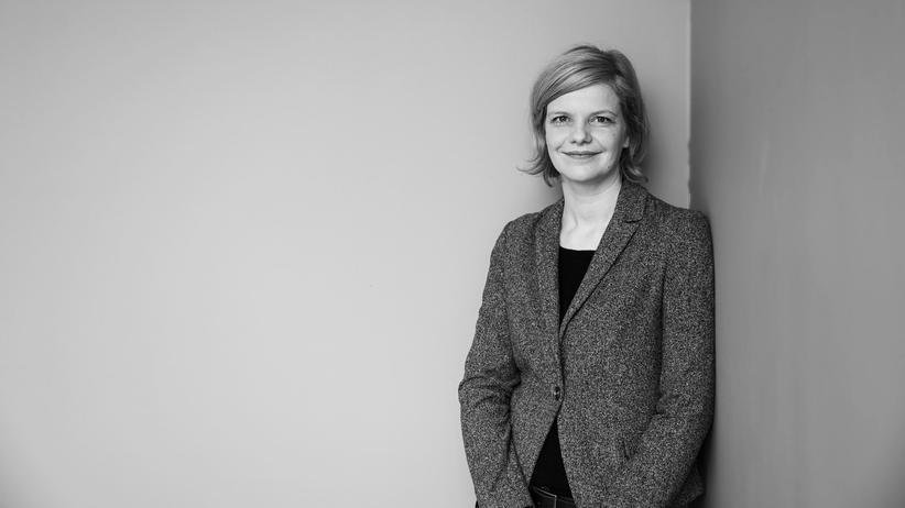 Janka Oertel, schwarz-weiss-Fotografie vor grauer Wand.