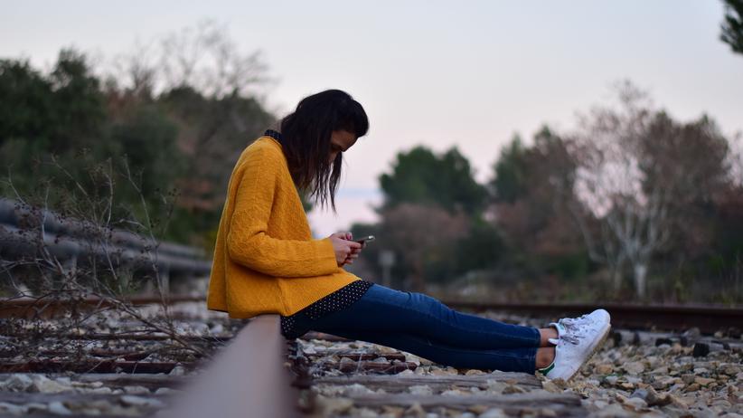 Leistungsschutzrecht: Eine Frau sitzt auf einem alten Bahngleis und starrt auf ihr Smartphone.
