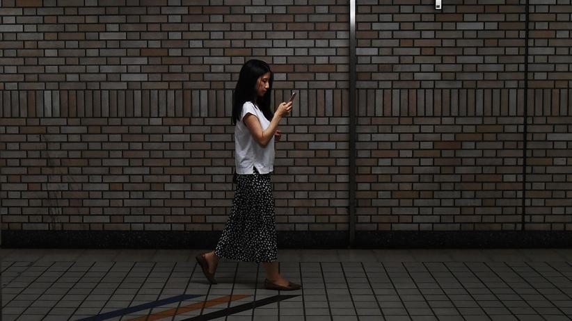 CES: Eine Frau schaut auf ihr Smartphone, während sie durch einen Bahnhof in Tokio läuft. Durch Social-Media-Dienste wie Twitter können Menschen weltweit miteinander kommunizieren.