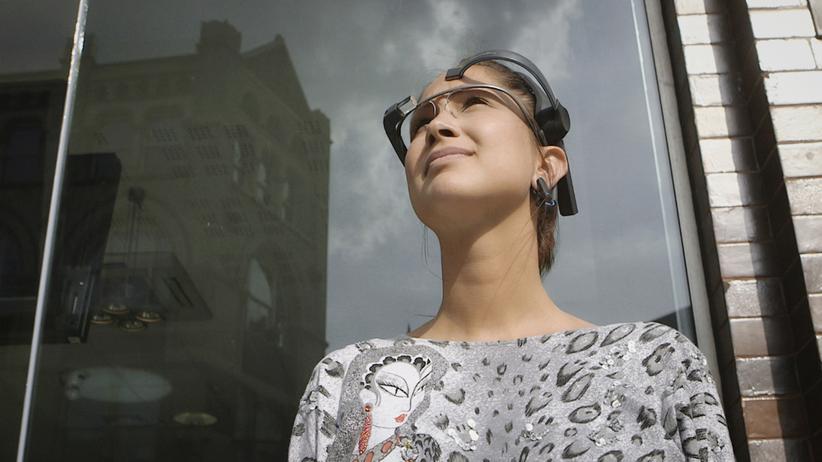 Ein Modell trägt die Datenbrille Google Glass sowie den EEG-Sensor Neurosky MindWave.