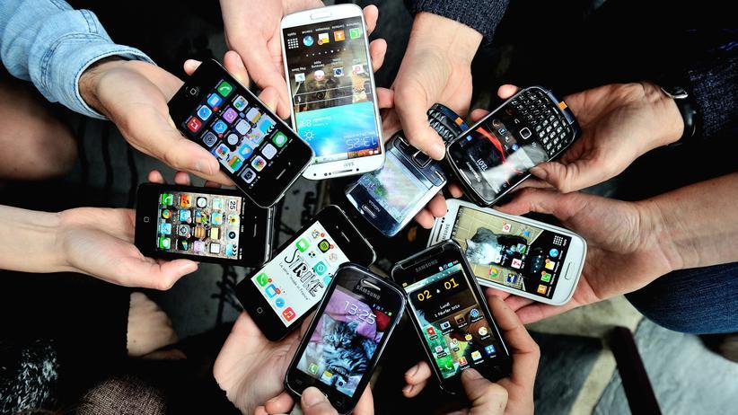 Smartphone-Besitzer zeigen auf einer Messe ihre Geräte.