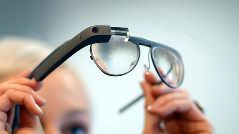 Eine Frau setzt die Datenbrille auf – oder ab.