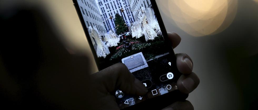 Ein Mann fotografiert den Weihnachtsbaum im Rockefeller Center in New York