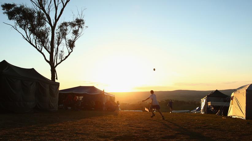 Urlaub: Jugendliche spielen Football auf einem Campingplatz in Brathurst, Australien.